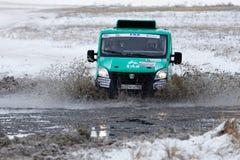 4WD集会卡车克服一个半冻池塘 图库摄影