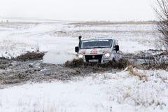 4WD集会卡车克服在积雪中的一个半冻池塘 免版税库存图片