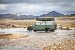 4WD car wades river in Iceland Stock Photos