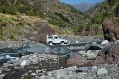 4WD crossing creek. Four wheel drive driving through stream bed in the canyon Barranco de las Angustias, Valley of Fear, between Caldera de Taburiente and the Stock Photos