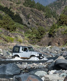 4WD crossing creek. Four wheel drive driving through stream bed in the canyon Barranco de las Angustias, Valley of Fear, between Caldera de Taburiente and the Stock Images