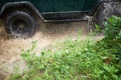 4WD fording a shallow stream at speed. Causing a splash of water from the wheels in a close up low angle view Royalty Free Stock Images
