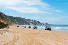 4wd pojazdy przy tęczą Wyrzucać na brzeg z coloured piasek diunami, QLD, Australia zdjęcia stock