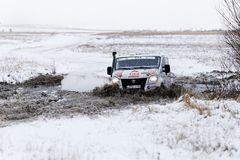 4WD rally truck overcomes a half-frozen pond among snow-covered Royalty Free Stock Images