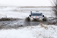 4WD rally vehicle overcomes a half-frozen pond Royalty Free Stock Photos