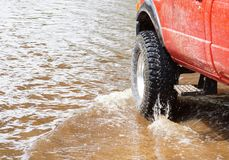A 4wd truck on flooded road. A 4wd truck running through a flooded road Royalty Free Stock Photos