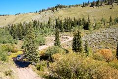 4WD vehicle driving through an alpine valley. Along a winding dirt road between evergreen trees viewed high angle Royalty Free Stock Photo