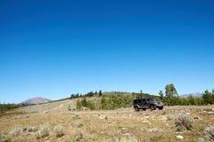 4WD vehicle driving through mountainous terrain Royalty Free Stock Image
