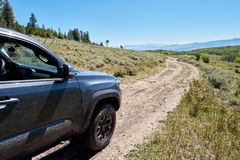 4WD vehicle driving through mountain scenery Stock Photo