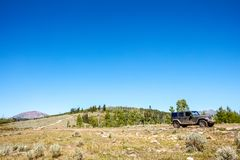 4WD vehicle driving through the mountains. On a winding dirt track during a summer expedition into the wilderness Stock Photos
