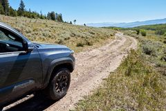4WD vehicle driving on a narrow dirt road. Through scenic mountain scenery in a close up view on the front side looking forwards at the environment Royalty Free Stock Photos
