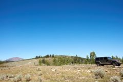 4WD vehicle driving through scenic mountains. On a narrow dirt road along a grassy ridge under a sunny blue sky Royalty Free Stock Image