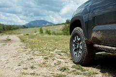 4WD vehicle parked alongside a mountain road. 4WD vehicle parked alongside a mountain dirt road on a cloudy day facing towards distant peak over a grassy plateau Stock Photos
