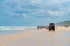 4wd vehicles at Rainbow Beach with coloured sand dunes, QLD, Australia. Rainbow Beach, QLD, Australia- December 30, 2017: 4wd vehicles at Rainbow Beach, a stock images