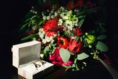 Wdding sonne dans le boîte-cadeau et le bouquet sur la table dans le doux vert Photo stock