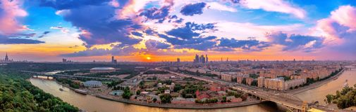 Wde angle vibrant panoramic view of sunset above Moscow city and cloud reflections in river with traveling boats and bridge. Wde angle panoramic view of sunset stock photos