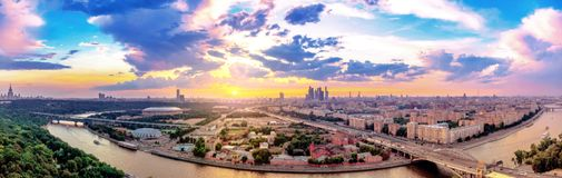 Wde angle vibrant panoramic view of sunset above Moscow city and cloud reflections in river with traveling boats and bridge. Wde angle panoramic view of sunset royalty free stock images