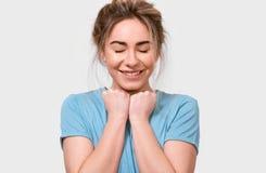 Wdzięczny młodej kobiety ono uśmiecha się i utrzymanie ręki na klatce piersiowej z zamkniętymi oczami, ubierającymi w błękitnej k obraz royalty free