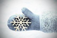 Wełny rękawiczka Z Drewnianym płatkiem śniegu, Śnieżny tło zdjęcia royalty free