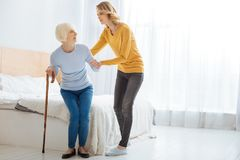 Caring young woman helping her aged granny to stand up. So weak. Calm attentive caring women supporting her aged worried grandmother while looking at her and Stock Photo