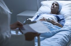 Dying patient with tumor. Weak and dying patient with malignant tumor lying in a hospital bed Royalty Free Stock Images