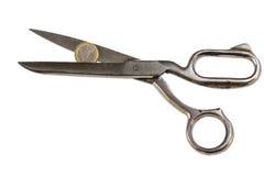 Weak Euro coin between scissors Stock Image