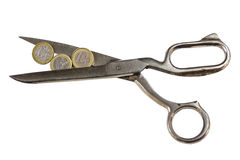 Weak Euro coins between scissors Stock Photo