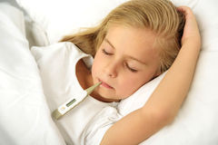 Weak girl with thermometer in mouth Stock Photos