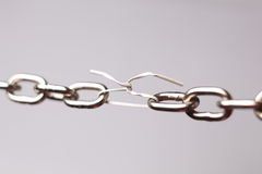 Weak Link. Weak plastic link joining the links of a steel chain Stock Photos