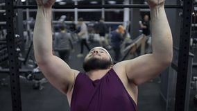 Weak obese male trying to pull up in gym, lack of self-confidence, insecurities stock video