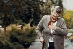 Weak senior woman with walking stick waiting for help during breathlessness attack stock photography