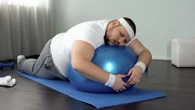 Weak-willed fat man relaxing on fitness ball, home workout break, laziness. Stock photo stock photos
