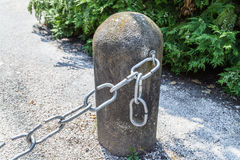 The weakest link. The link in the chain is opening: this weak link defines the real strength of this steel chain linked to bollard Stock Photography