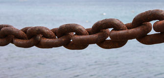 The weakest link. An old rusted chain link at the waterfront Stock Photography