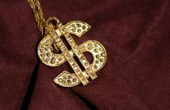 Wealth. Photo of a Gold Dollar Symbol on a Burgundy Background - Bling / Wealth Royalty Free Stock Photo