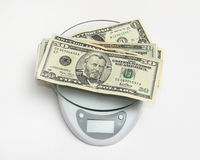 Wealth. US currency notes on a weighing scale Royalty Free Stock Photo
