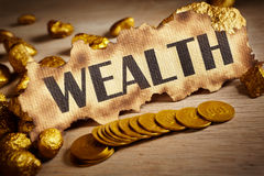 Wealth concept. Wealth written on vintage paper and stack of gold coins and gold rocks Royalty Free Stock Photography