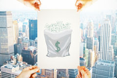 Wealth concept. Four hands holding paper with creative money sack sketch on city background. Wealth concept Royalty Free Stock Image