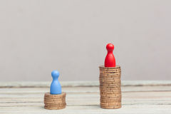 Wealth concept, red and blue pawn on coin stacks Royalty Free Stock Photo