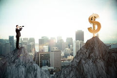 Wealth concept. Side view of young businessman on cliff looking at dollar sign through binoculars. Wealth concept. City background Stock Image