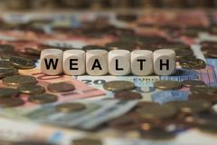 Wealth - cube with letters, money sector terms - sign with wooden cubes Stock Photo
