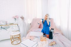 Wealth flaunting rich girl lifestyle shopping. Wealth flaunting. Rich girl lifestyle. Spoiled young lady in tiara taking selfie with money fan on bed after royalty free stock images