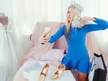 Wealth flaunting rich girl lifestyle social media. Wealth flaunting. Rich girl lifestyle. Social media. Blonde lady in tiara taking selfie with money fan on bed royalty free stock photography