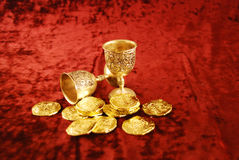 Wealth of gold and silver. Silver chalices with symbols of wealth amongst gold coins Royalty Free Stock Images
