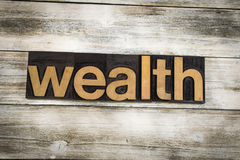 Wealth Letterpress Word on Wooden Background Stock Photos