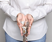 Woman holding coins in her hands. Wealth - person holding US coins in her hands Royalty Free Stock Images