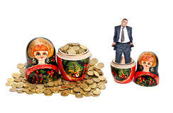 Wealth and poverty. Two Matryoshkas. One Matryoshka is full of coins and another is empty with poor businessman pulling out his pockets in it at white background royalty free stock image