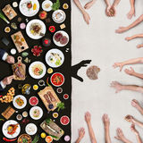 Wealth and poverty. View from above the table. A top view of a table with an abundance of food and a multitude of hands that stretch towards the bread Stock Photo