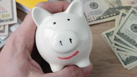 Wealth and savings money concept. Man draws a smile on a piggy bank stock video