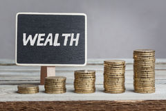 Wealth on sign with money stacks. Word Wealth in white chalk type on black board, Euro money coin stacks of growth on wood table Stock Photos